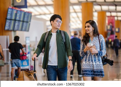 A young and photogenic Asian couple (Korean man, Indian girlfriend) smile as they walk in a futuristic airport. They are pulling their luggage behind them as they look for their check in counter.