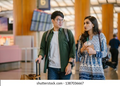 A young and photogenic Asian couple (Korean man, Indian girlfriend) smile as they walk and talk in an airport. They are pulling their luggage behind them on their way for a vacation overseas.