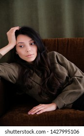 A young photogenic portfolio girl or model is lying on the couch looking away or down with a calm relaxed look. The concept of fashion and style, cosmetology, natural women's beauty, modeling.