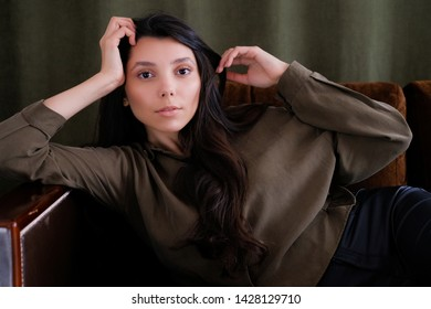 A young photogenic portfolio girl or model is lying on the couch looking at the camera with a calm look. The concept of fashion and style, cosmetology, natural women's beauty, modeling.