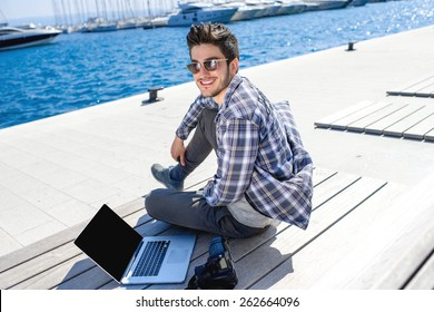 Young photographer in casual clothes sitting with laptop and camera on the sunbed near the sea with ships on background