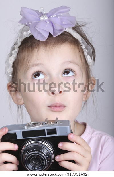 Young photographer, dreaming child holding an old vintage camera