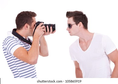young photographer during a photo shoot with a male model, on white background