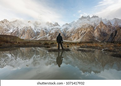 Young photographer looking at Passu Cathedral mountain in Pakistan and reflection on the water. Mountain landscape with reflection on the water