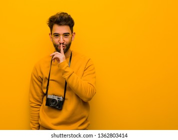 Young photographer man keeping a secret or asking for silence