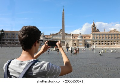 young photographer Take a photo in Piazza del Popolo  that means People s Square in Rome at the great obelisk