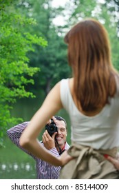 Young photographer takes photo of woman at summer green park.