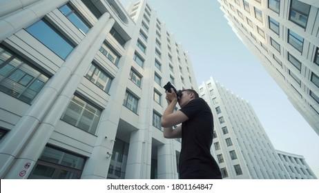 Jeune photographe photographie de l'architecture urbaine moderne. Action. Vue de dessous de gars photographiant l'architecture moderne avec caméra. Un photographe tire sur des immeubles de bureaux contre le ciel bleu