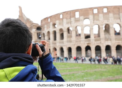 young photographer taking a picture of the famous Roman Colosseum amphitheater in winter in Rome Italy