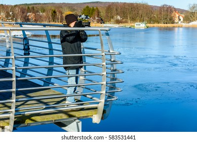 Young photographer taking picture while standing on bridge with icy water down below. Cold but sunny day in early spring or winter. Landscape in background.