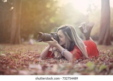 Young photographer taking a picture while lying in the woods