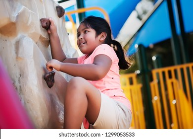 Young and physically active indian girl using her strength to conquer a rock climbing wall.