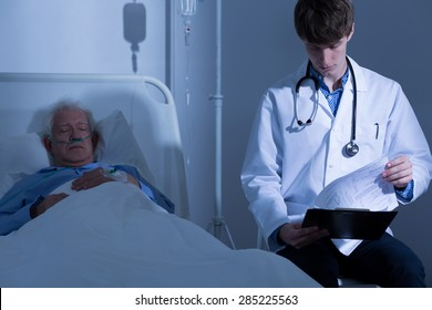 Young physician looking at his terminally ill patient's medical history