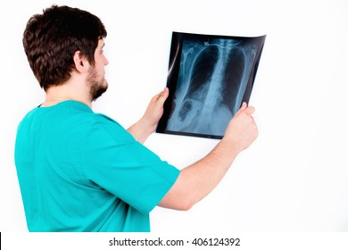 A young physician radiologist examines the picture, the white background. Uniform, experience.