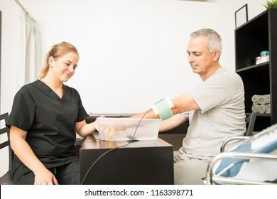Young physiotherapist giving electrotherapy to mature patient at table in hospital