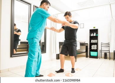 Young physiotherapist helping athlete to walk between cones in hospital