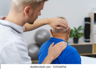 Young physiotherapist massaging the neck of senior patient in a physic room
