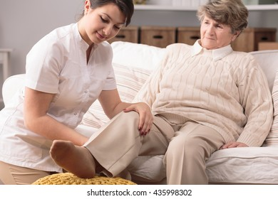 Young physiotherapist and senior woman sitting on sofa during exercises.