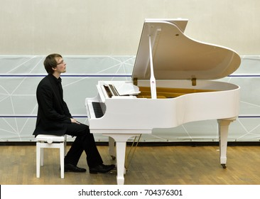 Young pianist sits in front of white grand piano