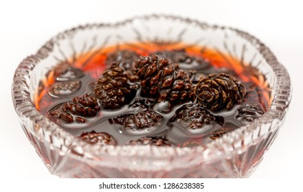 Young pine cones jam. Useful and tasty dessert. Traditional Siberian dessert - young pine cones jam. Glass ramekin of jam made from pine cones on a white background. on a white background