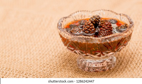 Young pine cones jam. Useful and tasty dessert. Traditional Siberian dessert - young pine cones jam. Glass ramekin of jam made from pine cones on a white background.