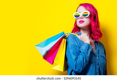 Young pink hair girl in rainbow sunglasses and blue shirt holding a colored shopping bags. Portrait on isolated yellow background