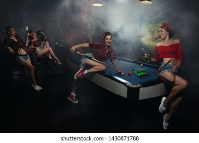 Young  pin-up Female Shooting Billiards with shots with absinthe instead of billiard balls