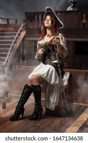Young pirate female with long red hair. Woman is wearing a black corset bustier, tricorn hat , gun belt and armed with a pistol and sword.