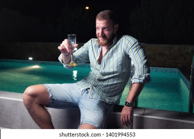 Young playboy sitting by the pool at night, flirting with a girl outside the frame, toasting to the good life sipping champagne from a glass, enjoying life concept