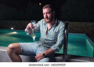 Young playboy sitting by the pool at night, toasting to the good life, sipping champagne from a glass, enjoying life concept
