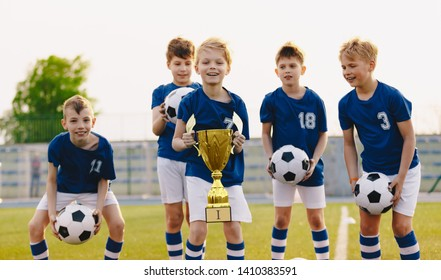 Young players of soccer team lift up the golden cup trophy after winning the final soccer match. Children celebrrate success in sports