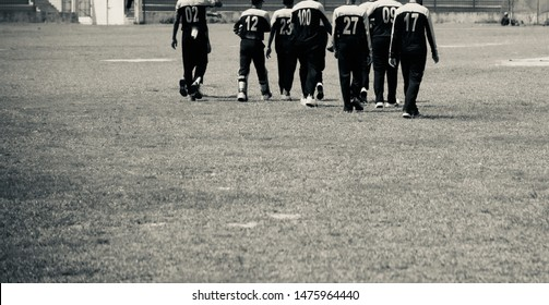 Young players are walking together around a sports ground