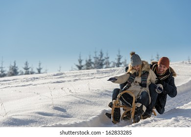 Young playful couple having fun in the snow sledging downhill