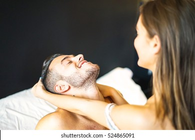Young and playful couple having fun in their bed - A sensuality girl pulling her boyfriend's hair - Passionate couple - Focus on man's face