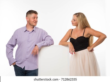 Young playful couple portrait of a confident businessman showing presentation, pointing placard gray background. Ideal for banners, registration forms, presentation, landings, presenting concept.