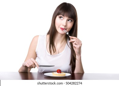 Young playful happy woman sitting in front of plate with delicious strawberry tart cake in dough basket, holding knife and fork, deciding to try sweet dessert, studio, white background, isolated