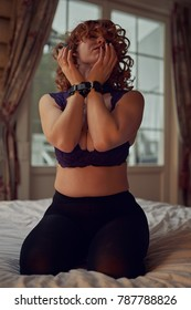 Young playful redheaded woman in handcuffs in cozy country house interior