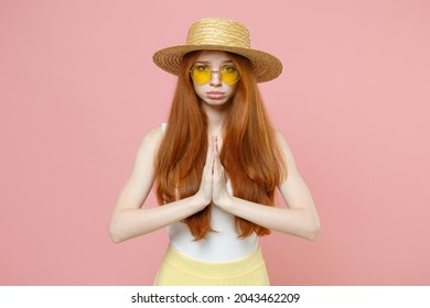 Young pleading hopeful nice woman 20s ginger long hair in straw hat glasses summer clothes hands folded in prayer gesture, begging about something isolated on pastel pink background studio portrait