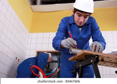 Young plumber cutting grey pipe