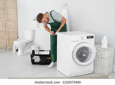 Young plumber fixing washing machine in bathroom