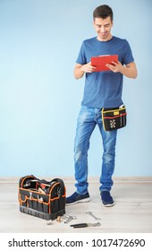 Young plumber with tool bag and clipboard against color wall