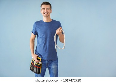 Young plumber with tool belt and flexible tube on color background