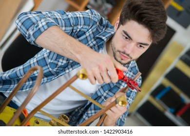 young plumber using blowtorch for soldering copper fittings