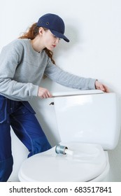young plumber woman near a flush toilet