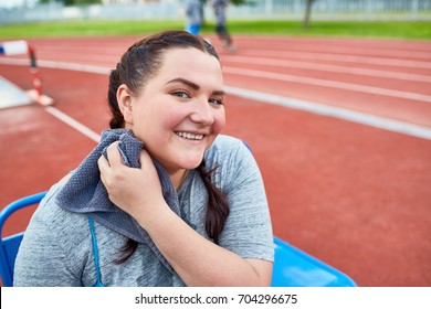 Young plump female drying sweat from her neck after sports training