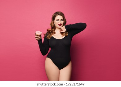 Young plump woman with bright makeup in black bodysuit is holding donut in her hand and posing at pink background, isolated with copy space. Concept of xxxl fashion and junk food