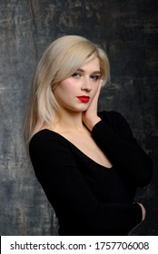 Young plump woman with bright makeup in black bodysuit is posing at dark background, isolated with copy space. Concept of xxxl fashion and junk food