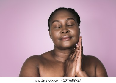 Young plus size African woman with a perfect complexion, smiling and standing with her eyes closed and hands on her cheek against a pink lavender colored background