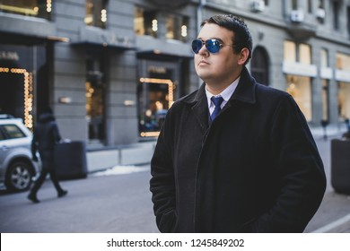 Young plus size man in city streets, plump people concept, one in big city life. Image of overweight businessman at downtown
