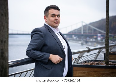 Young plus size man relaxing and enjoying the view city, plump people concept, one in big city life. Image of overweight businessman at downtown